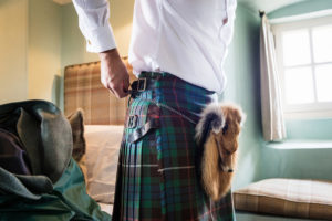 Groom getting dressed into kilt for wedding at Fenton Tower